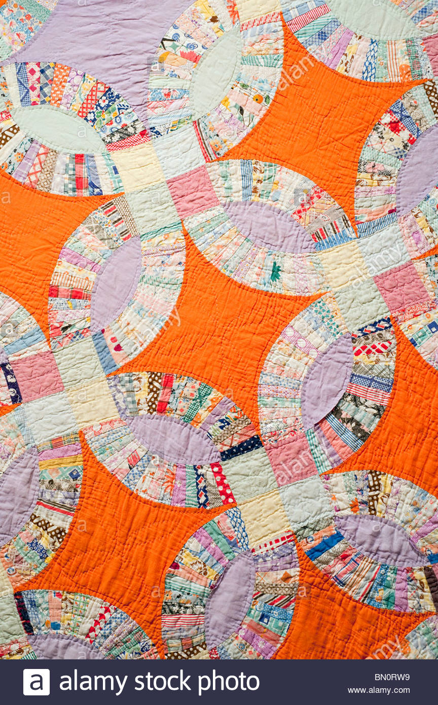 1920's 1930's Hand Made Wedding Ring Quilt details with Orange Diamonds Pattern. Traditional American Craft - Stock Image