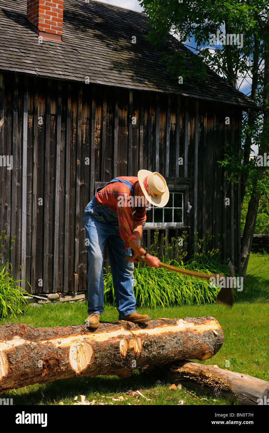 Man chopping wood to score timbre while hewing a log at Lang Pioneer Village - Stock Image