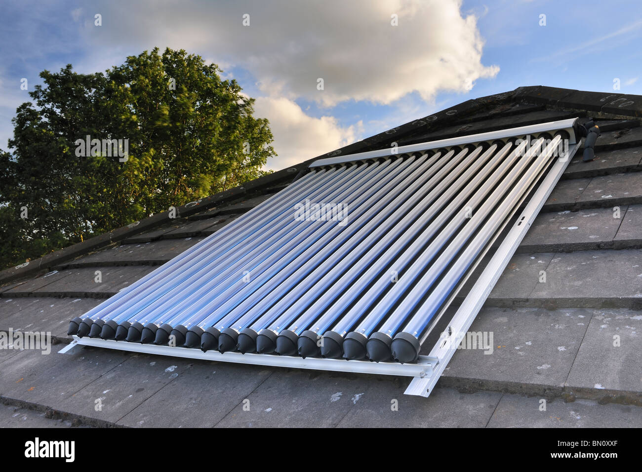 Solar Power. Solar vacuum/evacuated tubes on a domestic house roof in the UK - Stock Image