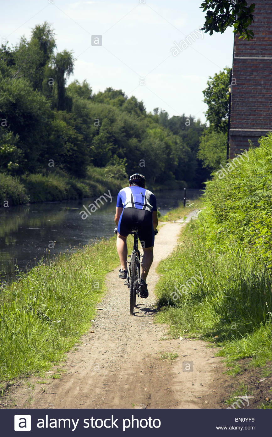 A cyclist on National Cycle Route 5, that is also the towpath for the Birmingham to Wolverhampton canal in the West Stock Photo