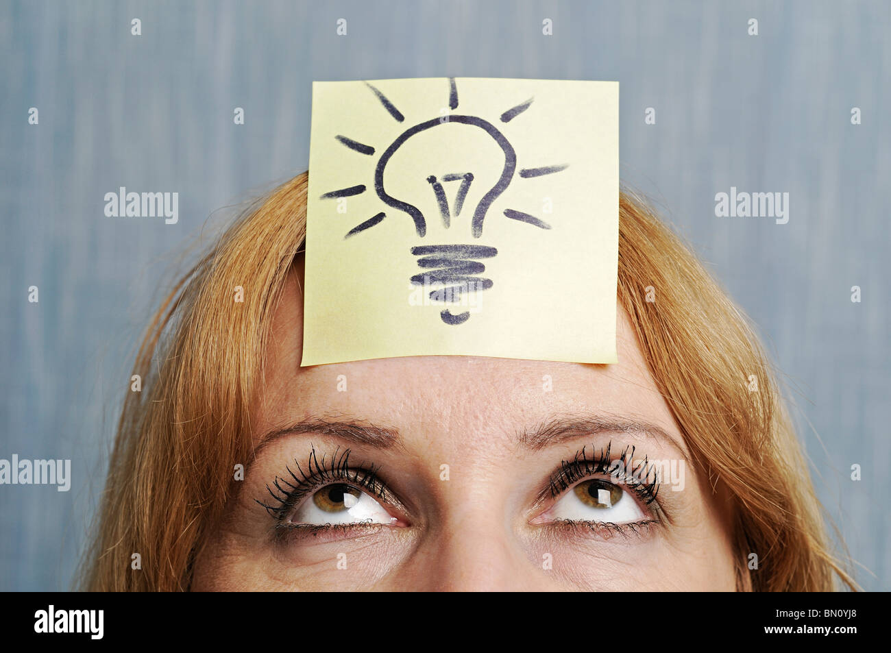 Ideas, Woman with a Drawing of a Lightbulb on Her Head. - Stock Image