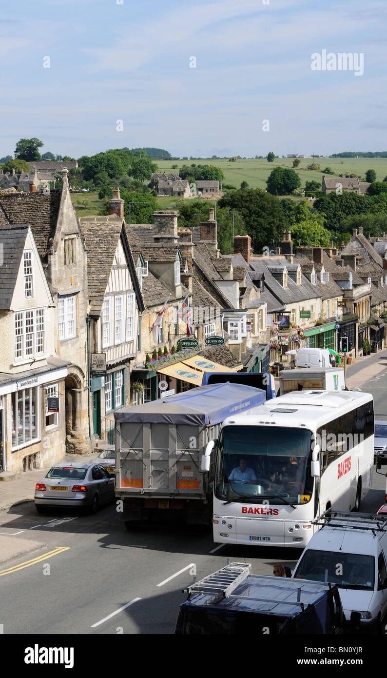 Traffic congestion in the Cotswolds town of Burford Oxfordshire where a tour bus and grain lorry are almost locked - Stock Image
