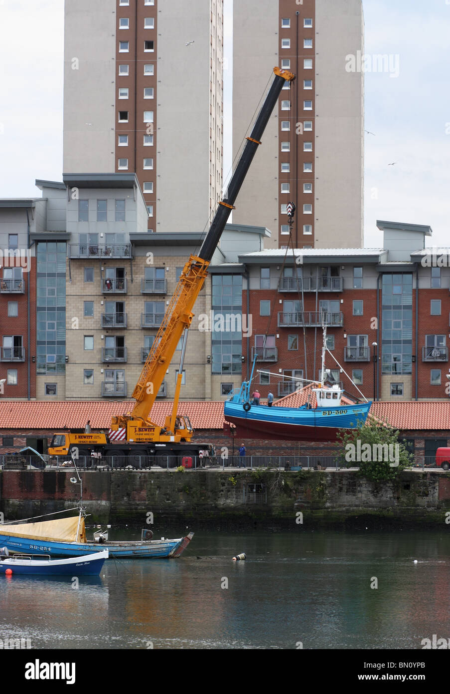 The wooden fishing vessel SD390 Isabella is lowered into the river Wear by a portable crane following  a refit. - Stock Image
