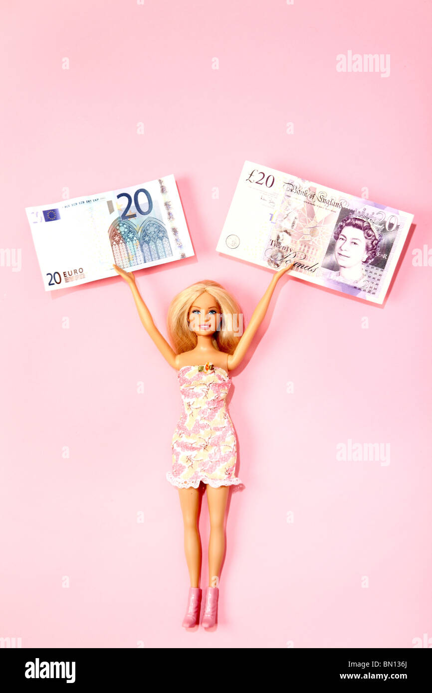 Barbie doll holding a €20 note and a £20 note in each hand, pink background - Stock Image