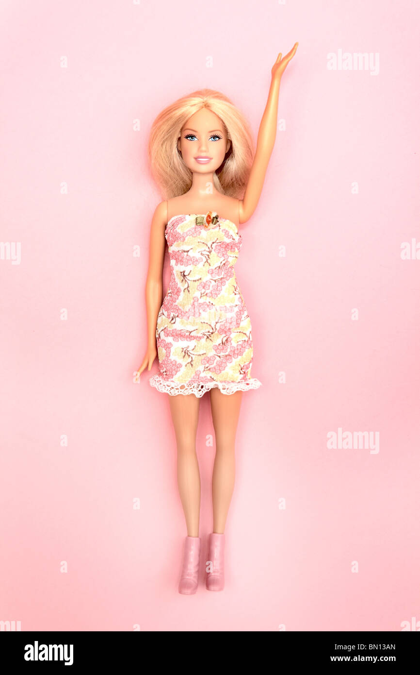 Barbie doll holding hand one hand up, pink background - Stock Image
