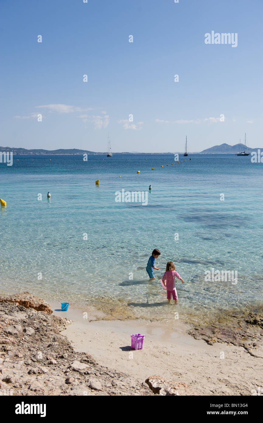 A brother and sister go netting for fish and shrimps on Formentor beach in Mallorca, Spain 2010 Stock Photo