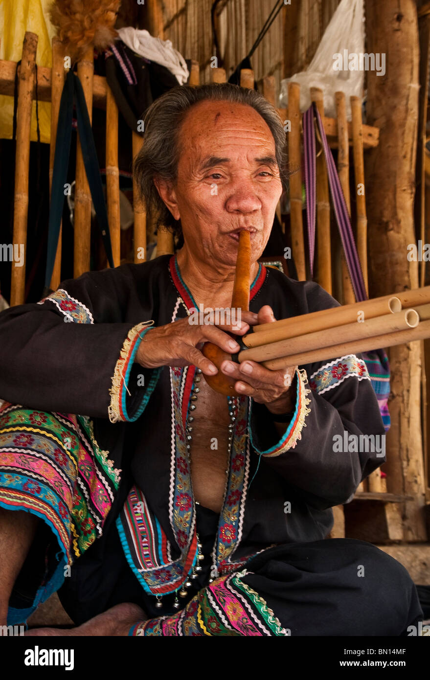 Man playing a type of flute at Baan Tong Luang, village of Hmong people in rural Chiang Mai province, Thailand. - Stock Image
