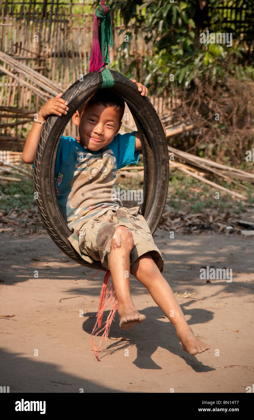 Young boy playing in in tire swing at Baan Tong Luang, village of Hmong people in rural Chiang Mai Province, Thailand. - Stock Image