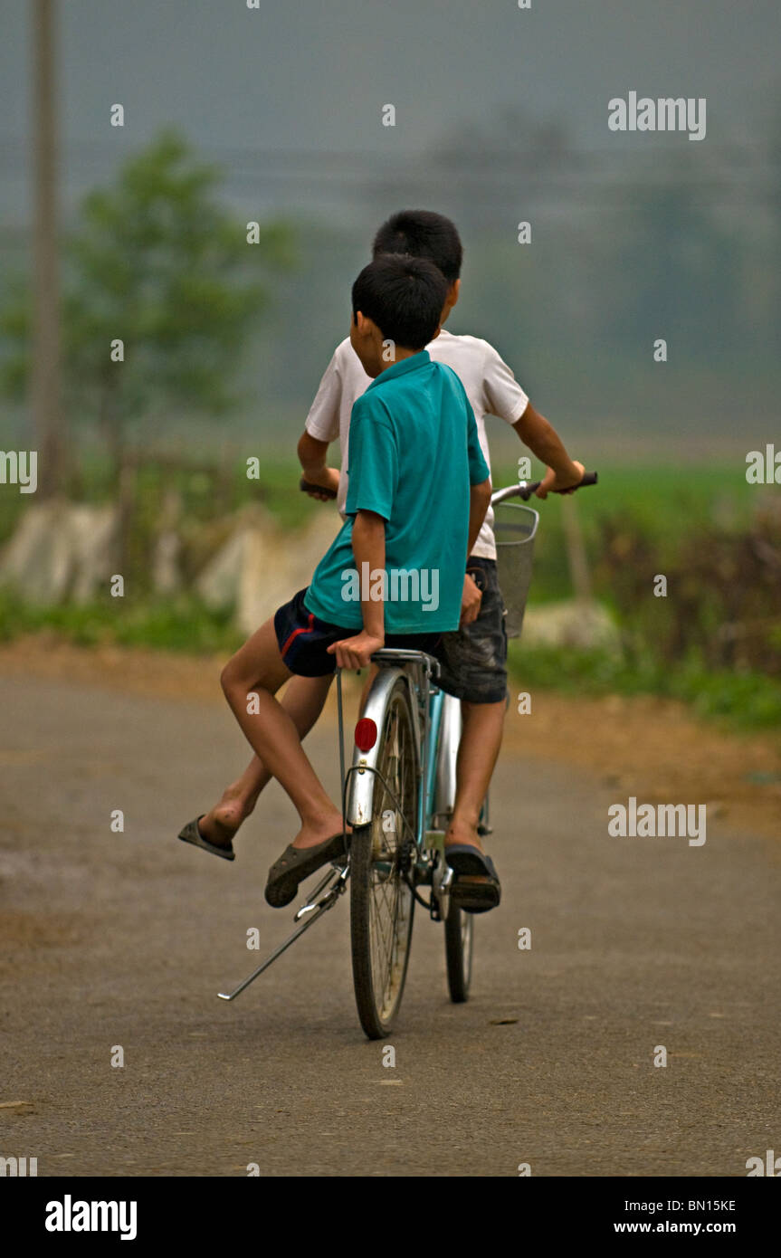 Two kids (children) riding a cycle in Mai Chai, north Vietnam - Stock Image