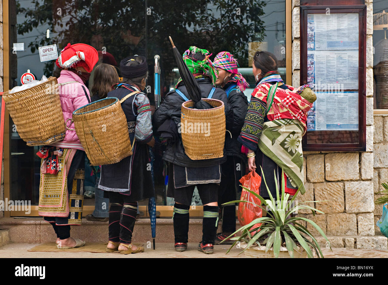 Local woman hawkers outside a restaurant in a market in Sapa, north west Vietnam - Stock Image
