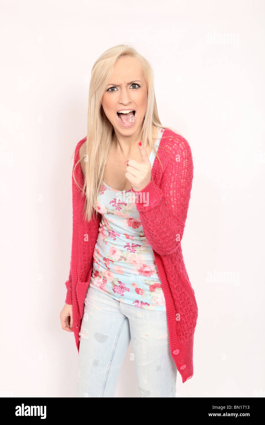 Young blonde woman angry expression pointing and shouting at camera, cut out - Stock Image