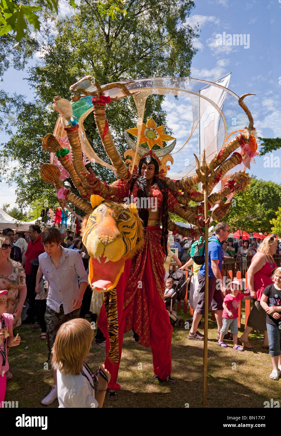Stilt-walking actor portraying the Hindu goddess Durga, walking through the crowd to attract an audience; Glasgow - Stock Image