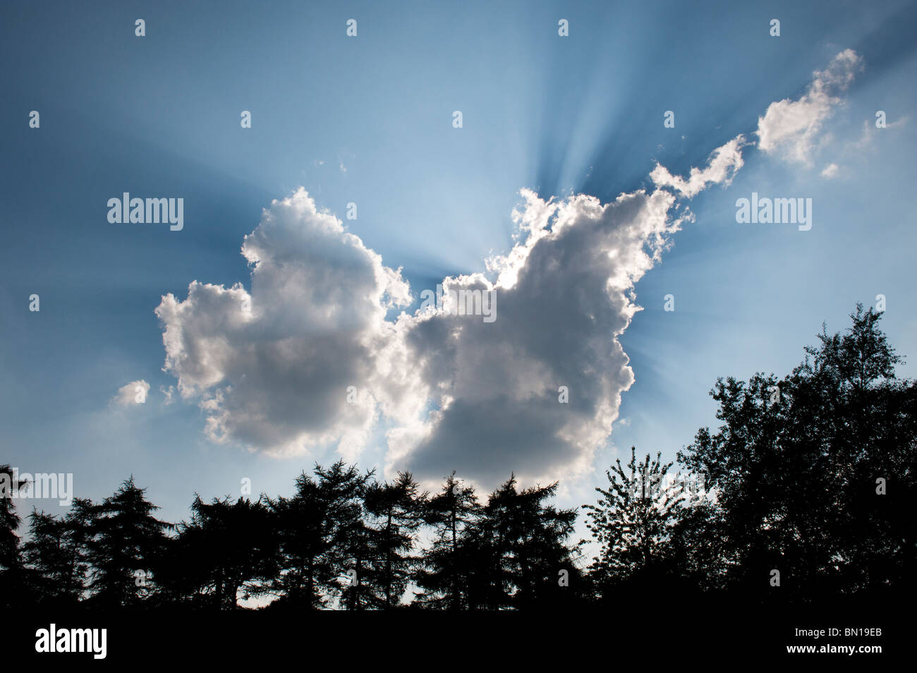 Dramatic sunrays behind a cloud in the english countryside. Oxfordshire, England - Stock Image