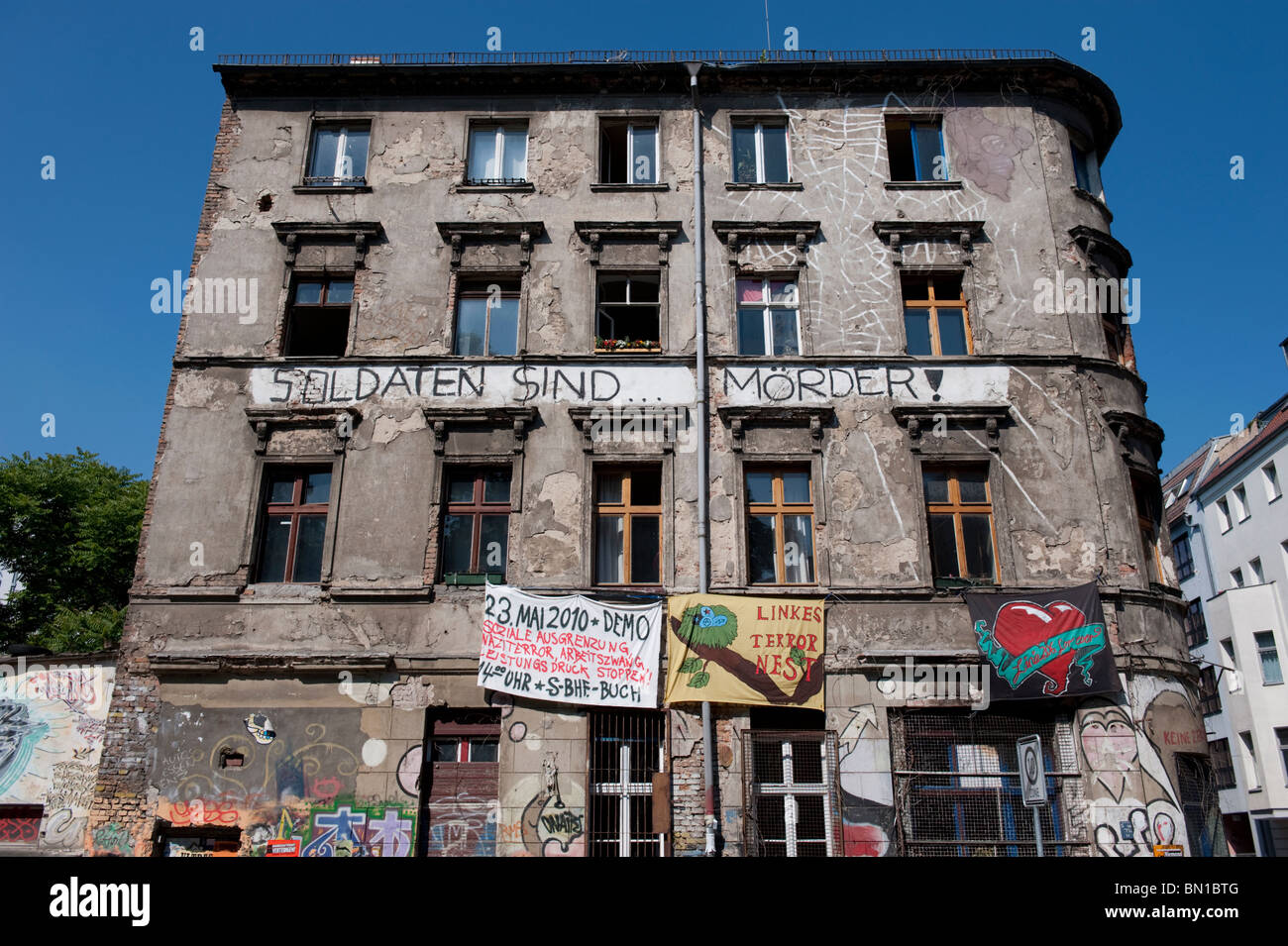 Old apartment building with squatters living inside and protest banners hanging on wall in Mitte Berlin Germany - Stock Image