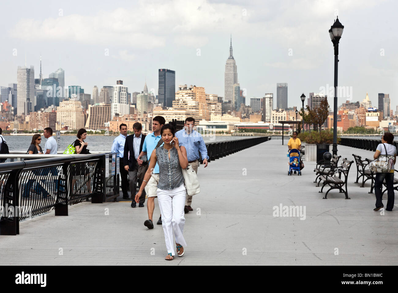 commuters swiftly disembark New York Waterways ferry at Hoboken pier against magnificent backdrop of Manhattan skyline - Stock Image