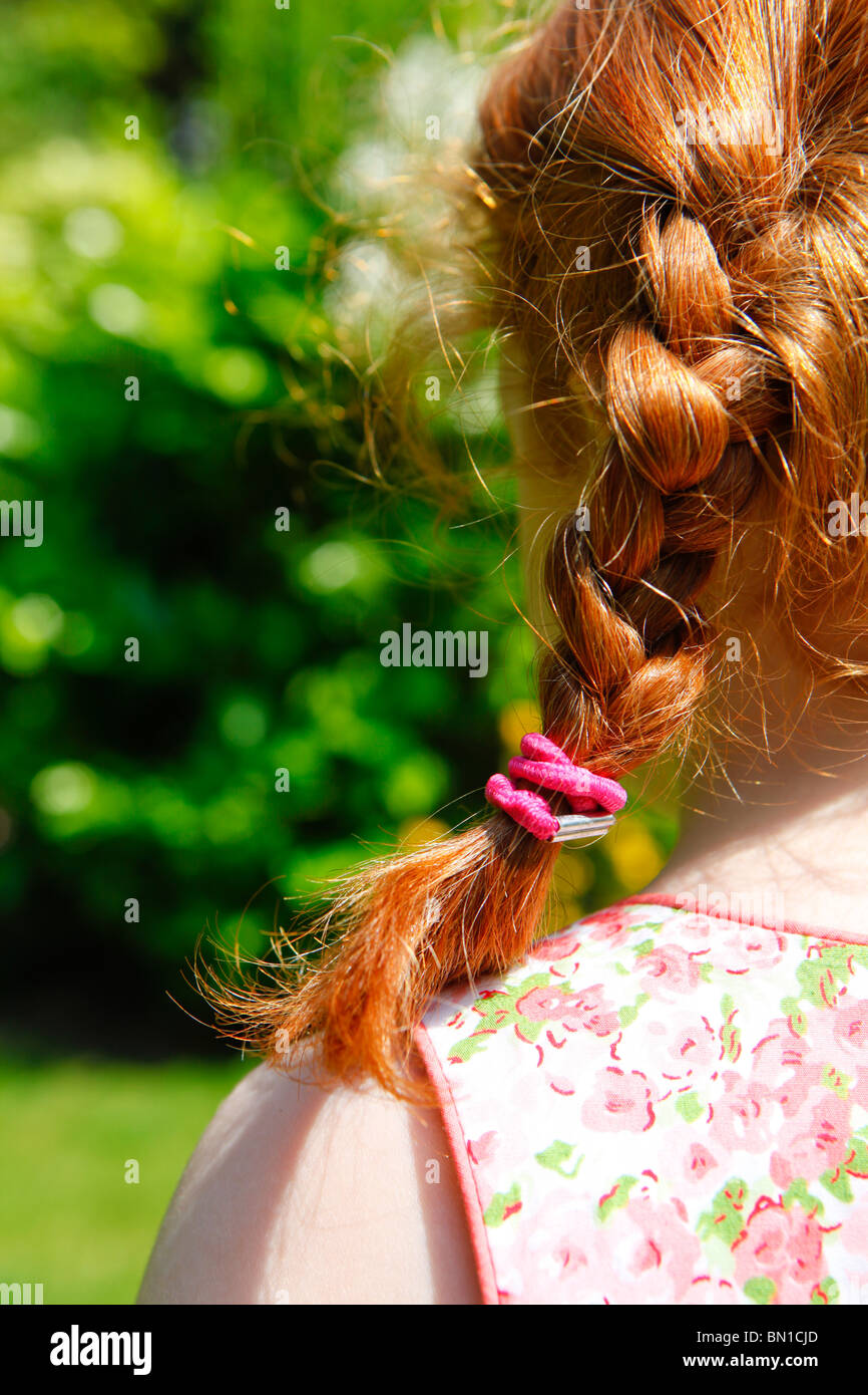 Red haired four year old girl in a garden with plaits. View from behind. - Stock Image
