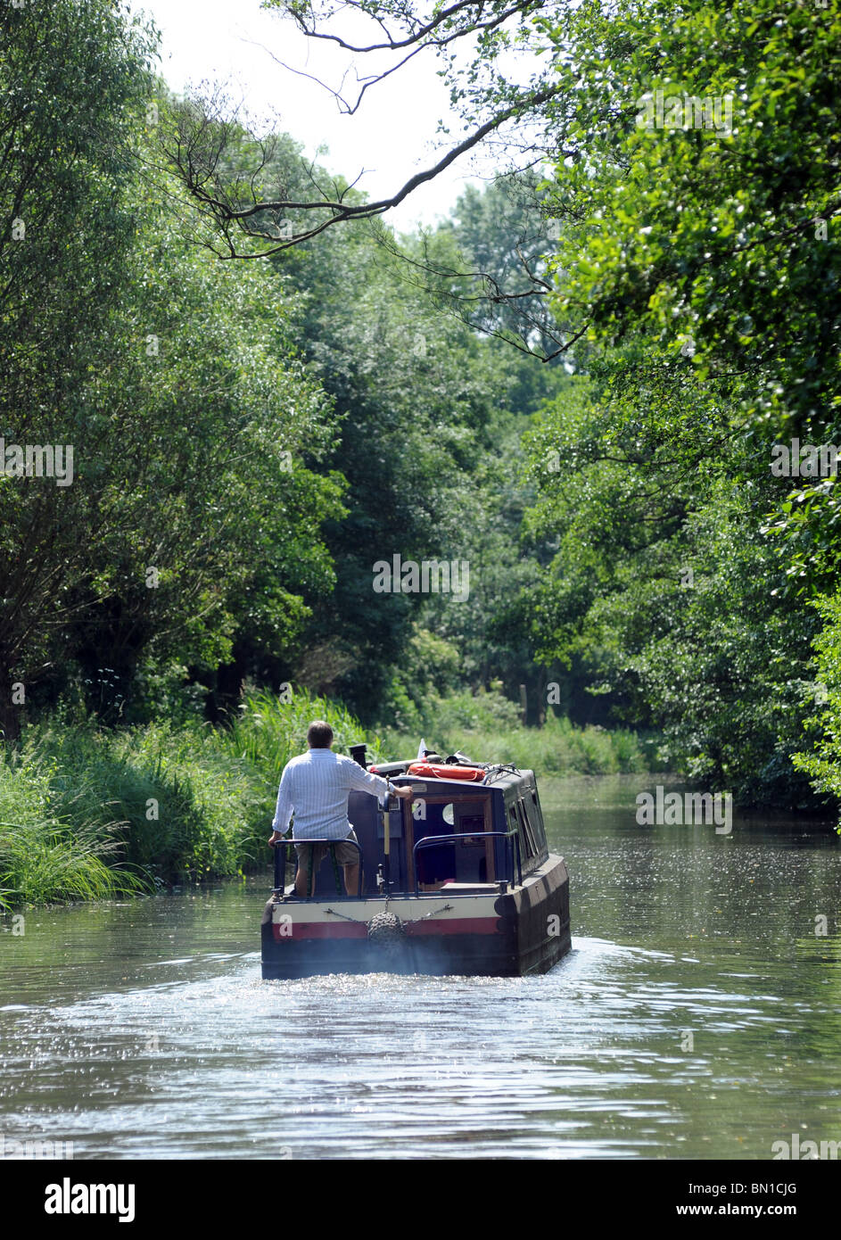A MAN STEERS A NARROWBOAT ALONG A BRITISH CANAL ,UK - Stock Image