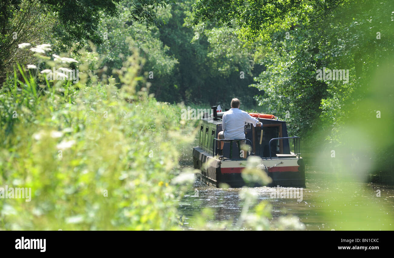 A MAN STEERS A NARROWBOAT  BARGE ON A BRITISH CANAL RE HOLIDAYS LEISURE RETIREMENT RELAXATION WATERWAYS HOBBIES - Stock Image