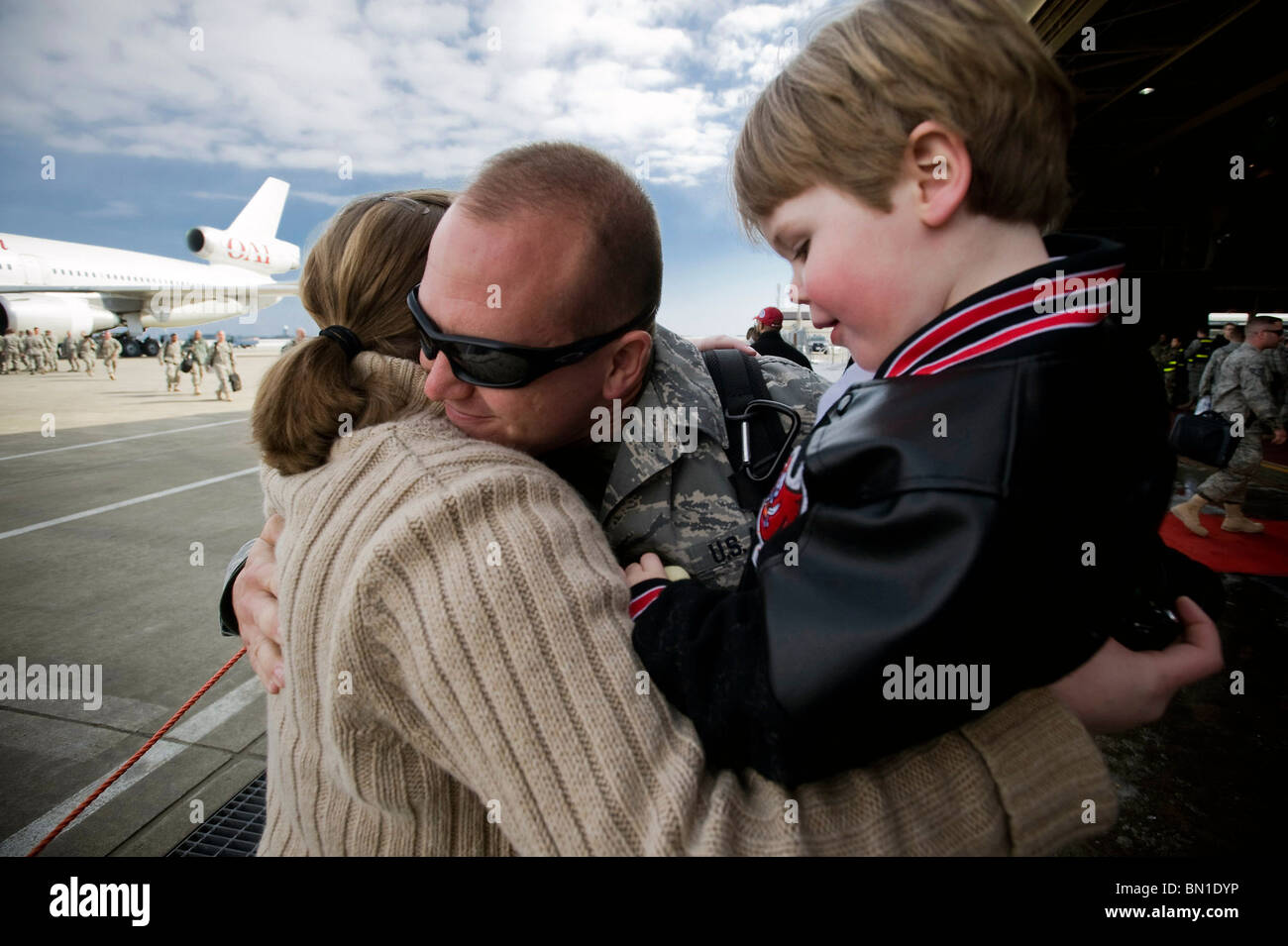 Staff Sgt. Adam Yeo hugs his family March 1 at Misawa Air Base, Japan. - Stock Image