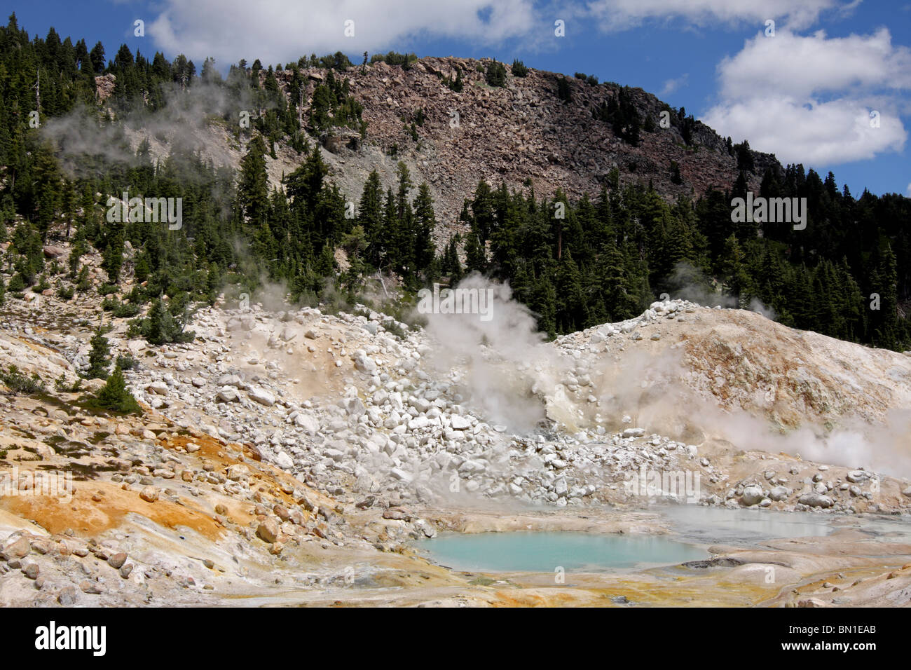 Steam rises from fumaroles alongside the boiling pools in the Bumpass Hell Geothermal Area of Lassen Volcanic National - Stock Image