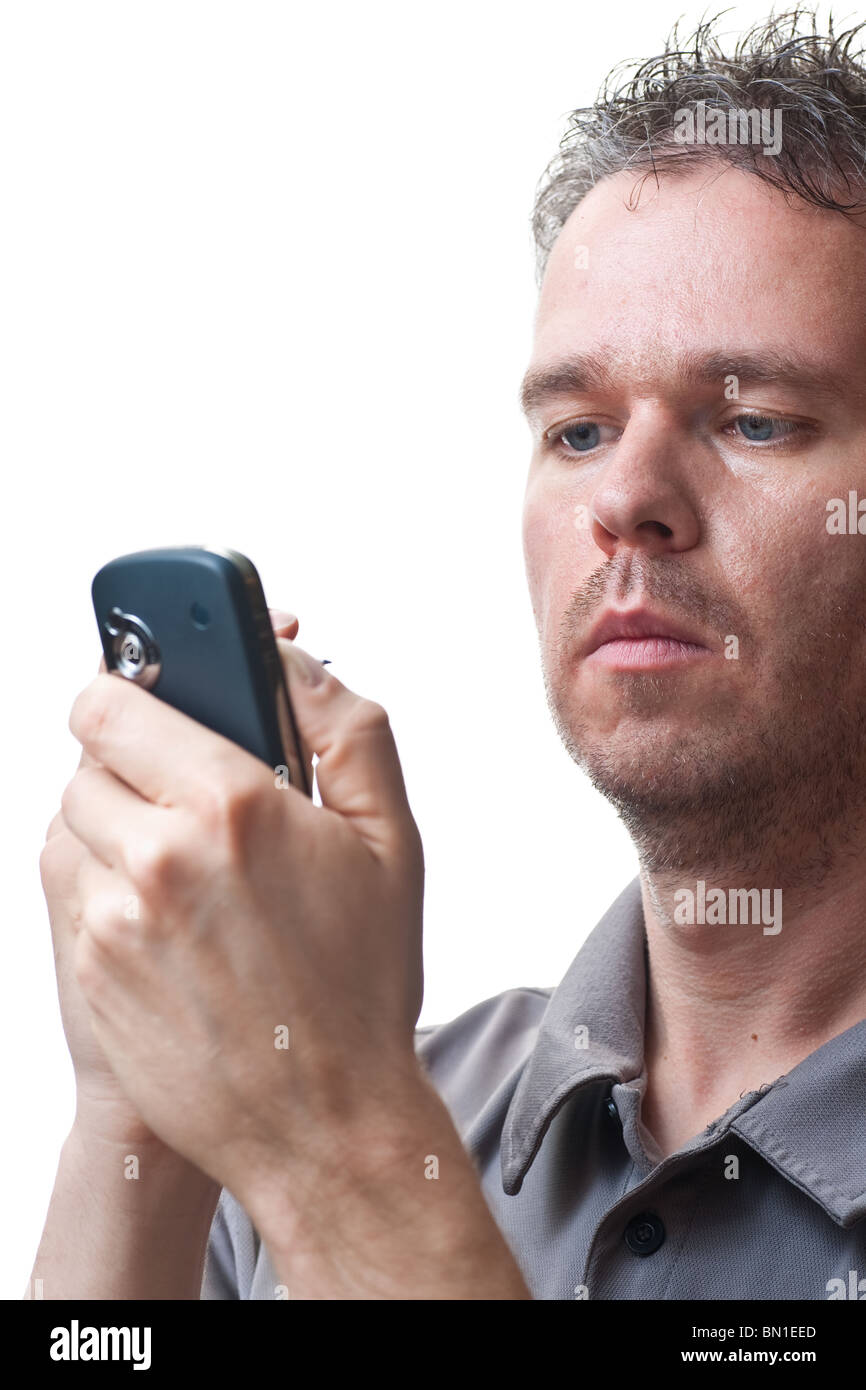 A man holding a PDA / Cel phone, looking at the screen while tapping on its screen, isolated on white. - Stock Image