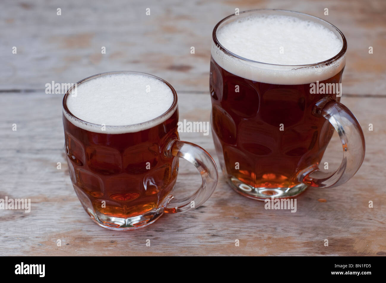 A half-pint and a full pint of 'Old Hooky' beer on a weathered outdoor table at a pub. - Stock Image