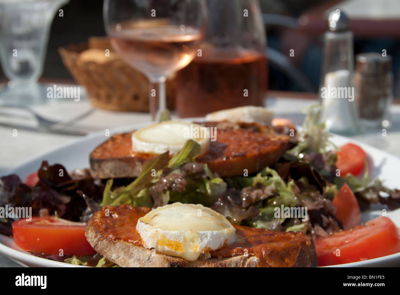 A lunch of Chevre Chaud salad at rose wine at an outdoor cafe in Montpellier. - Stock Image