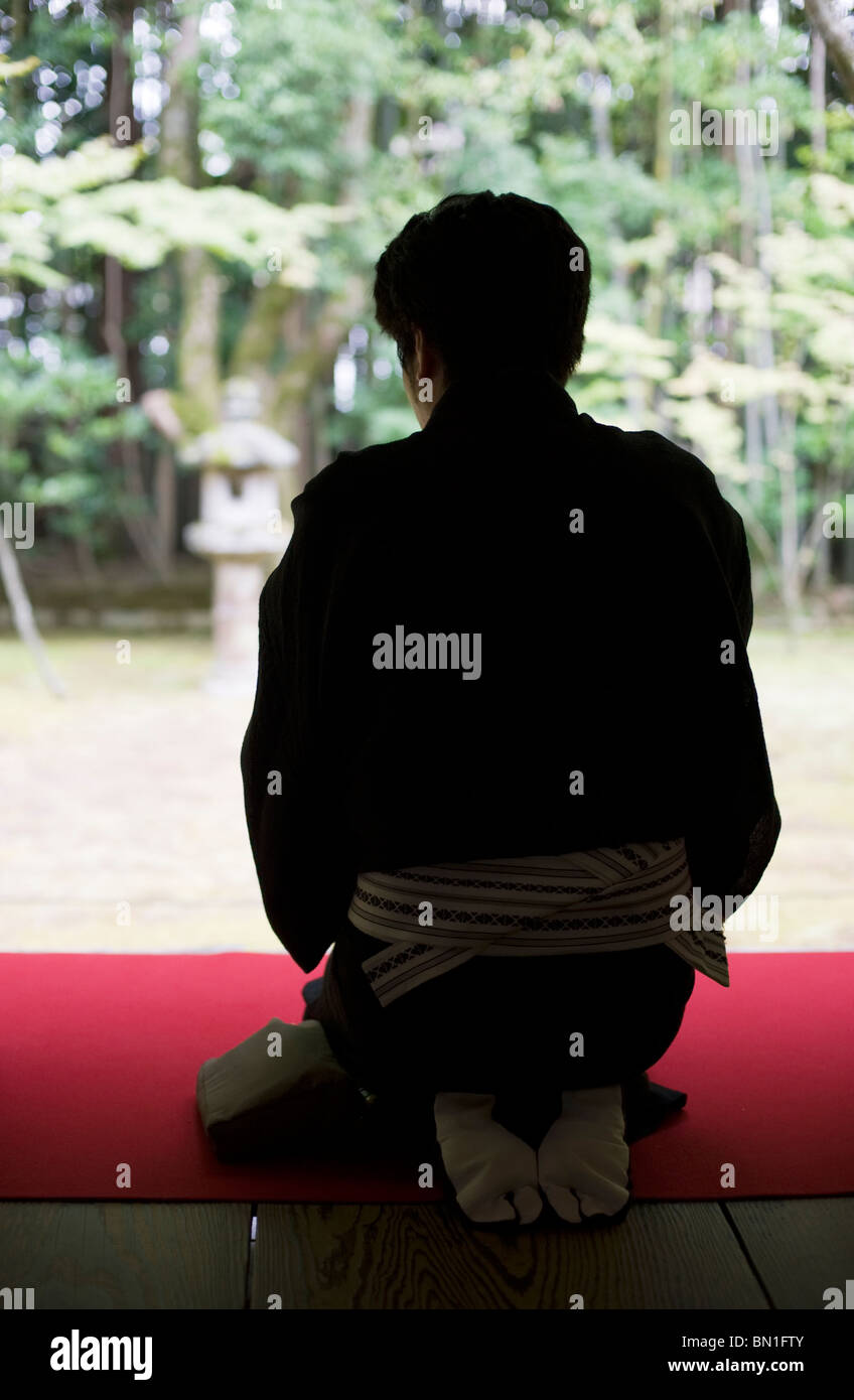 A Japanese man in a black kimono sits in the formal kneeling position to drink tea at Koto-in Temple, Daitokuji, - Stock Image