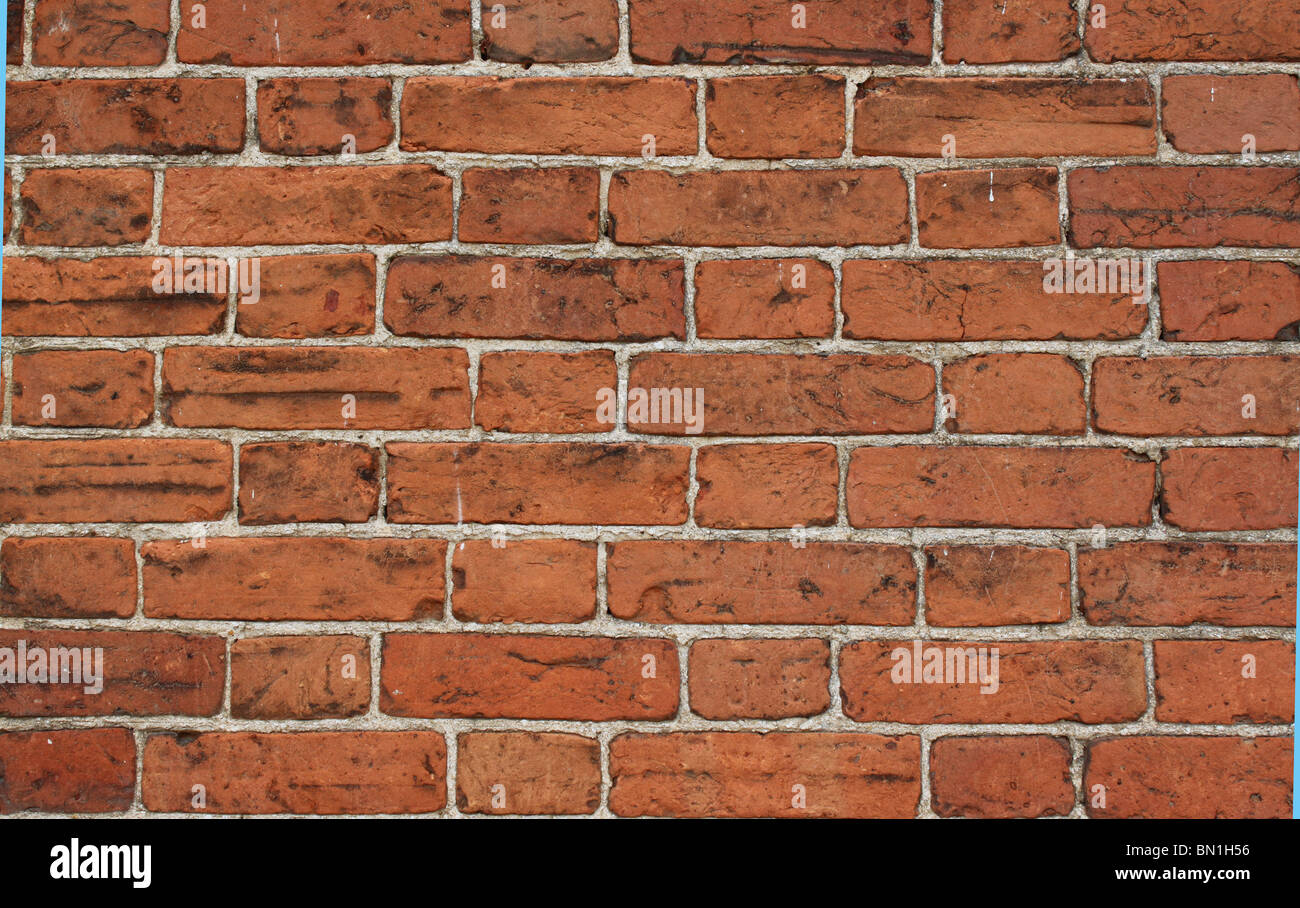 Red Brick wall with thin lime mortar joints. Suffolk red bricks. - Stock Image