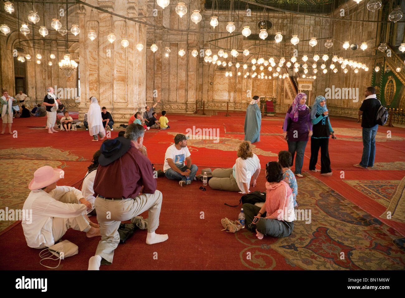 Tourists mingle with local people  inside the Mosque of Muhammad Ali Pasha, The Citadel, Cairo, Egypt - Stock Image