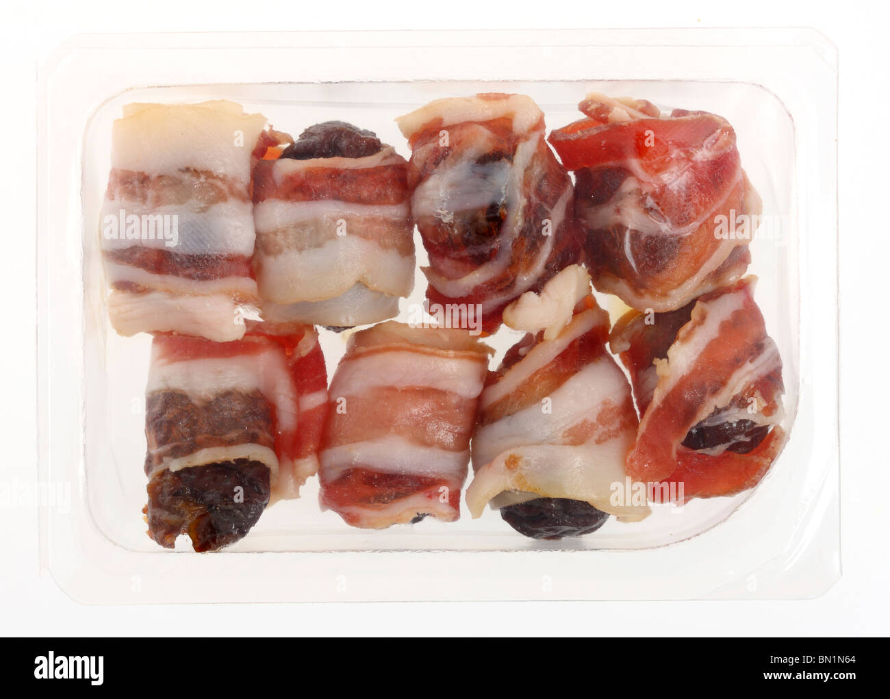 Dates wrapped in bacon, in a plastic box, convenience food from a supermarket. - Stock Image