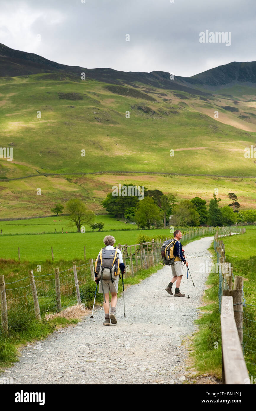 Walkers on the shore path on the east side of Buttermere in the Englaish Lake District. - Stock Image