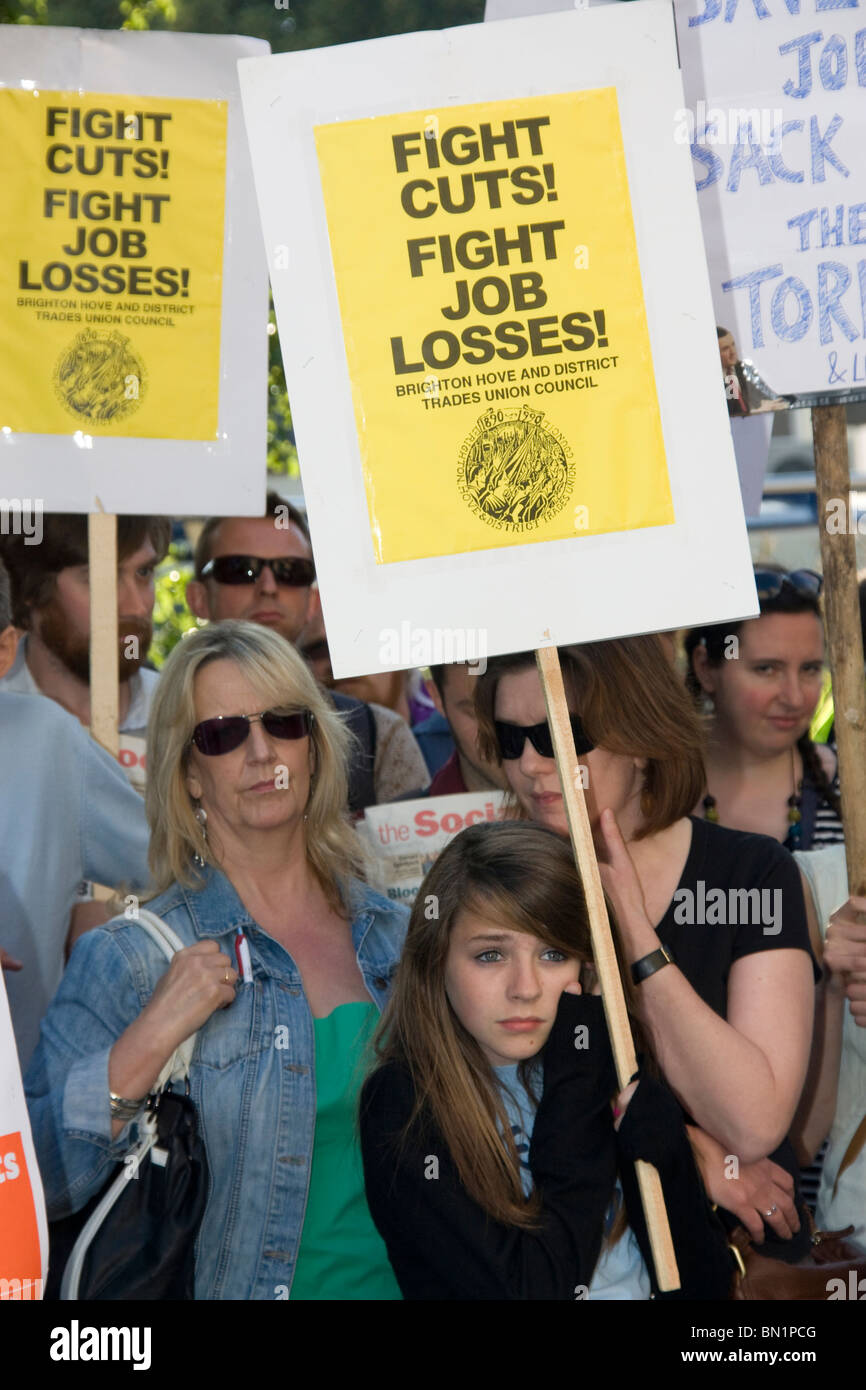 A crowd gathered outside Hove Town Hall to protest the Tory-Lib Dem 'emergency budget' and its attendant - Stock Image