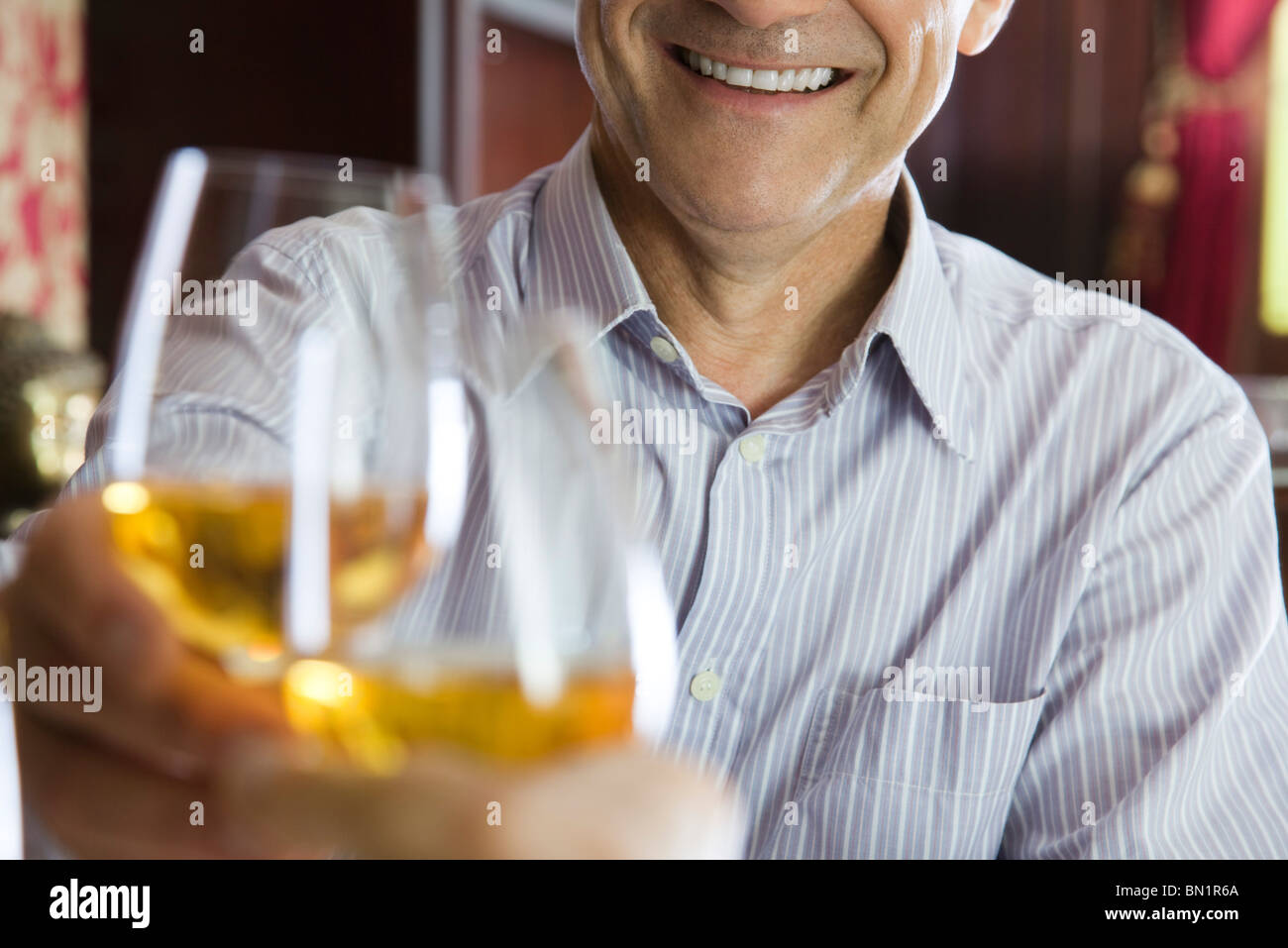 Man clinking glasses with companion in restaurant - Stock Image