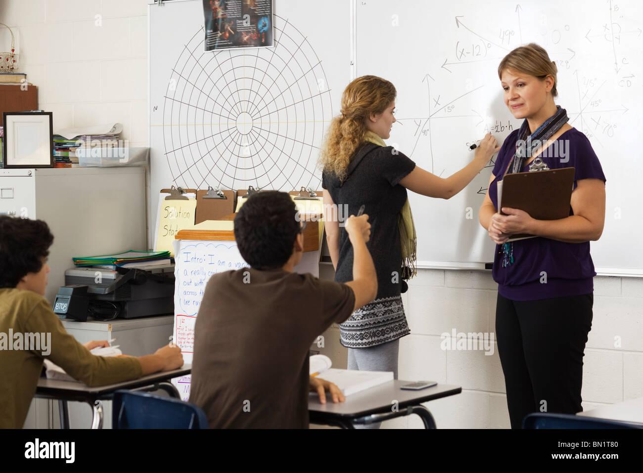 Woman teaching high school mathematics class - Stock Image