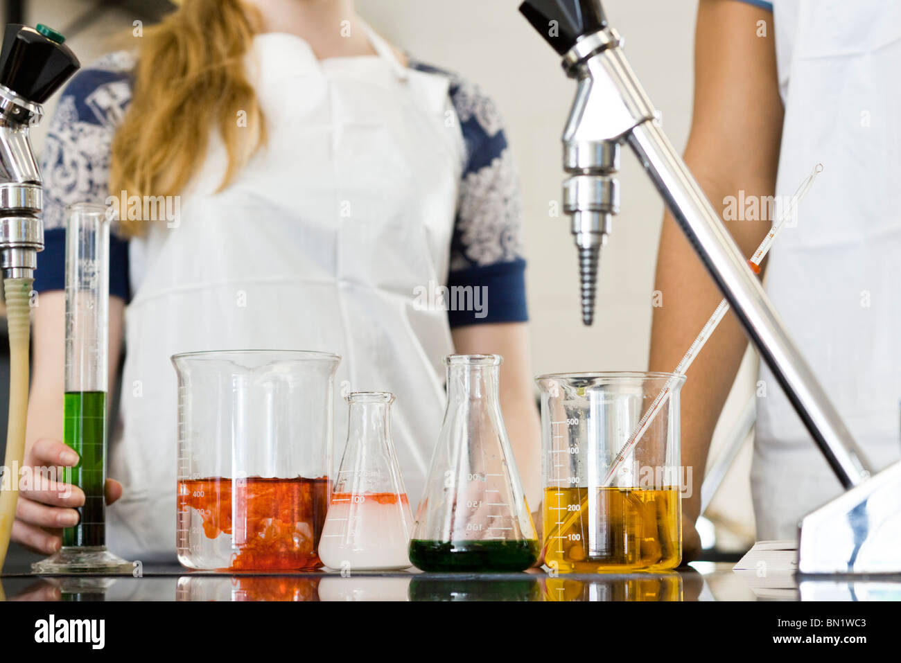 Students conducting experiment in chemistry class, cropped - Stock Image