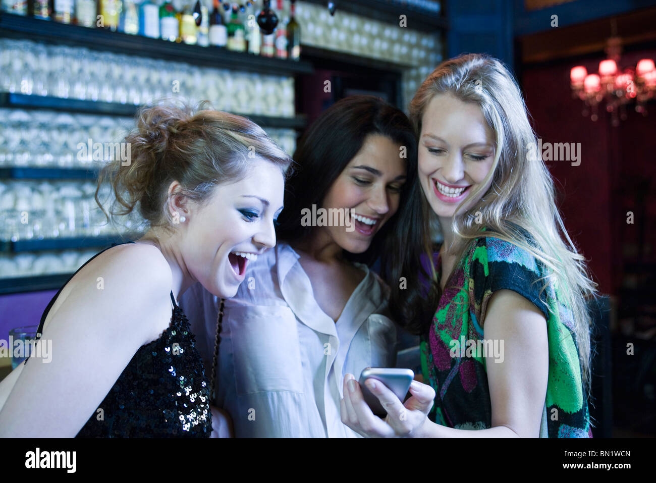 Friends together at bar, woman showing cell phone to others - Stock Image
