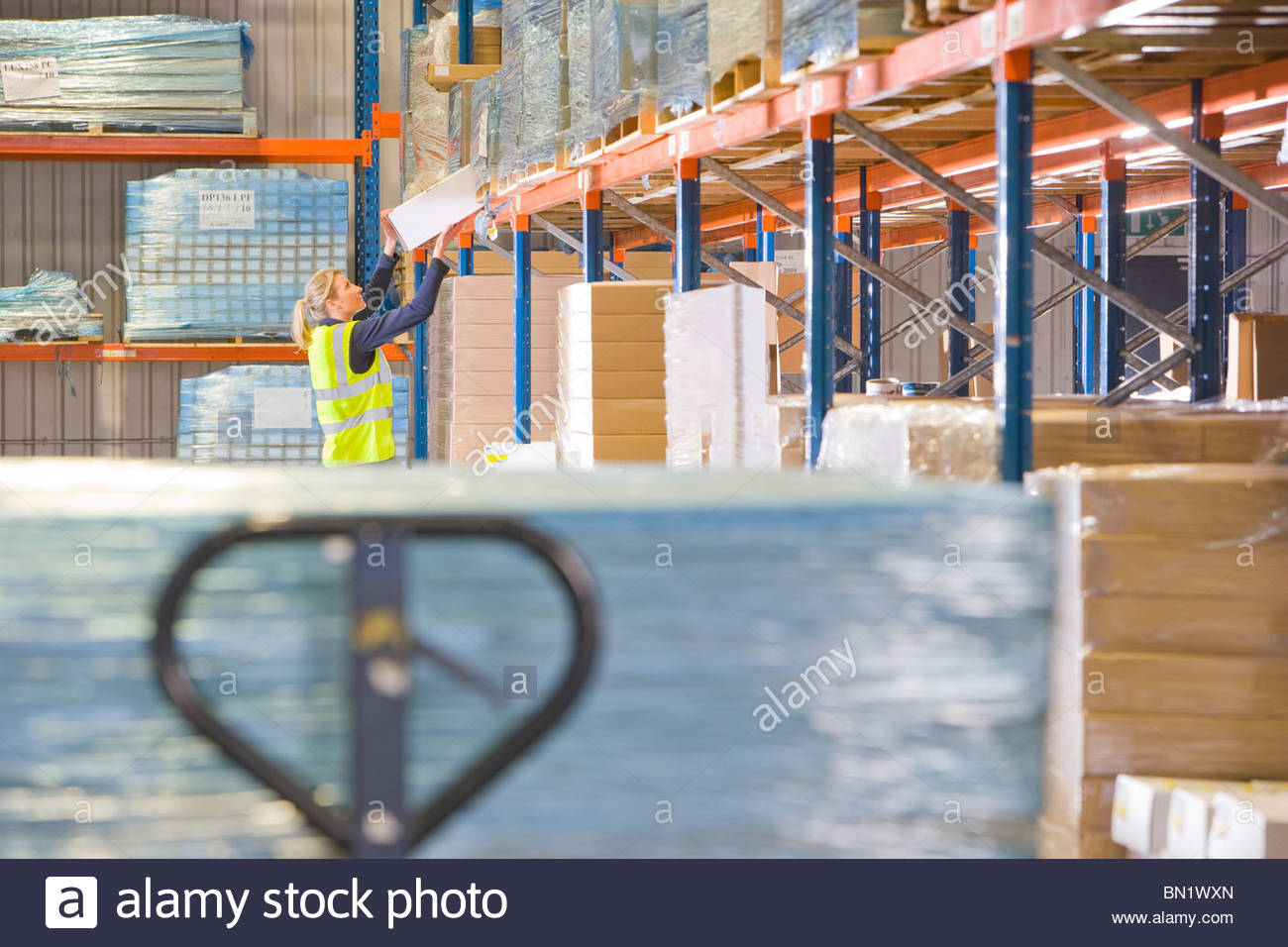 Female warehouse worker lifting box from shelf - Stock Image