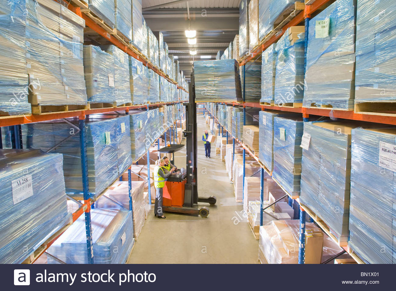 Warehouse workers moving boxes from shelf with forklift - Stock Image