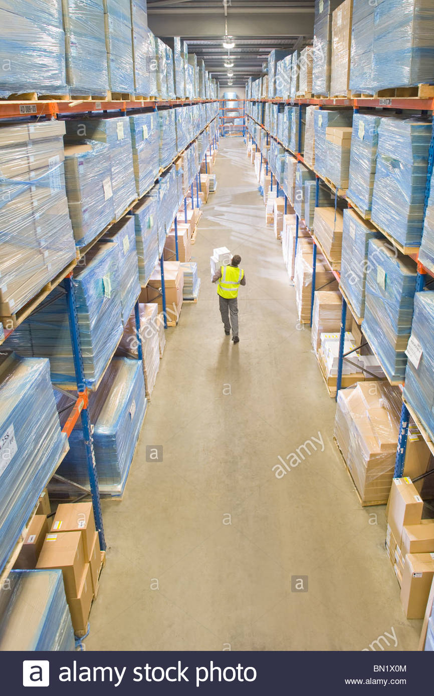 Warehouse worker carrying boxes in aisle - Stock Image