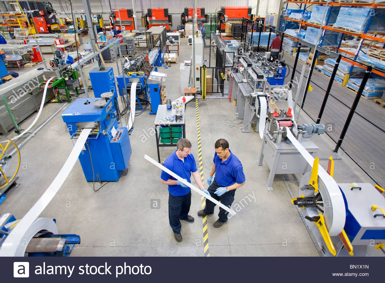 Workers inspecting aluminium light fitting in factory - Stock Image