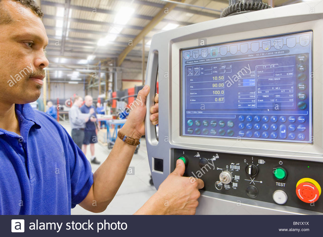 Worker operating computer controlled machinery in factory that manufactures aluminium light fittings - Stock Image