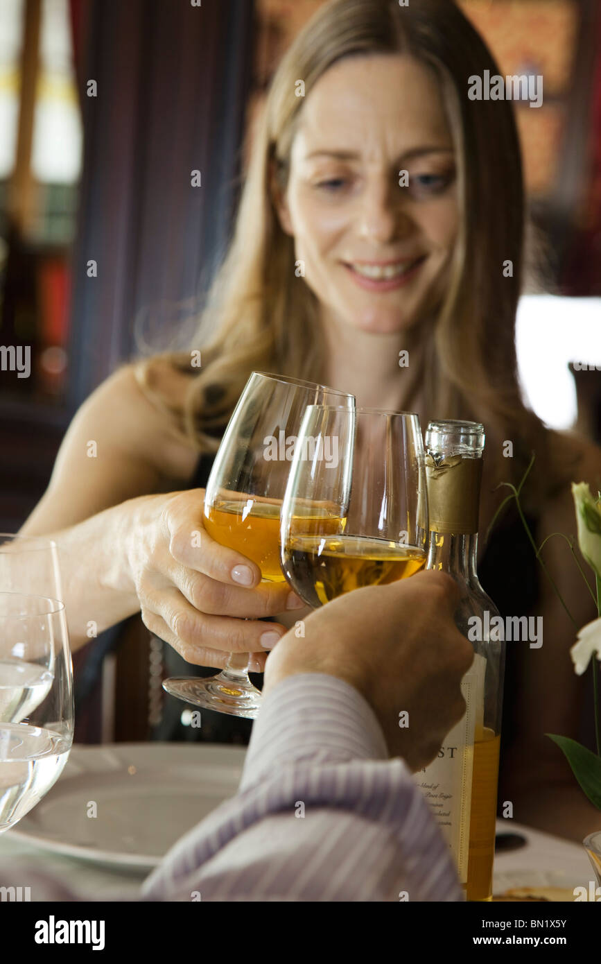 Woman clinking glasses with companion in restaurant - Stock Image