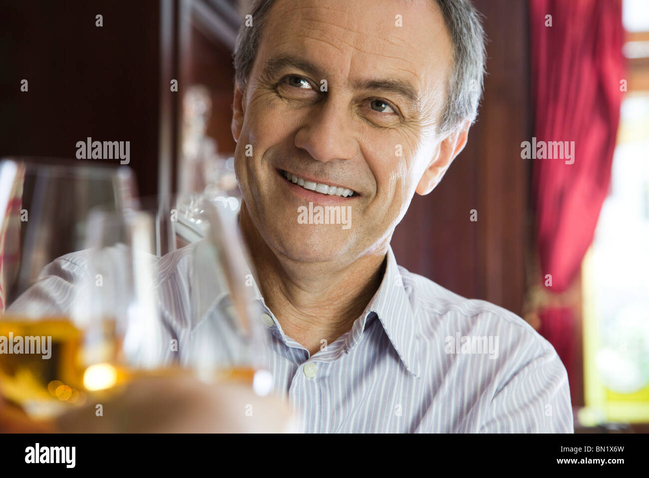Mature man clinking glasses with companion in restaurant - Stock Image