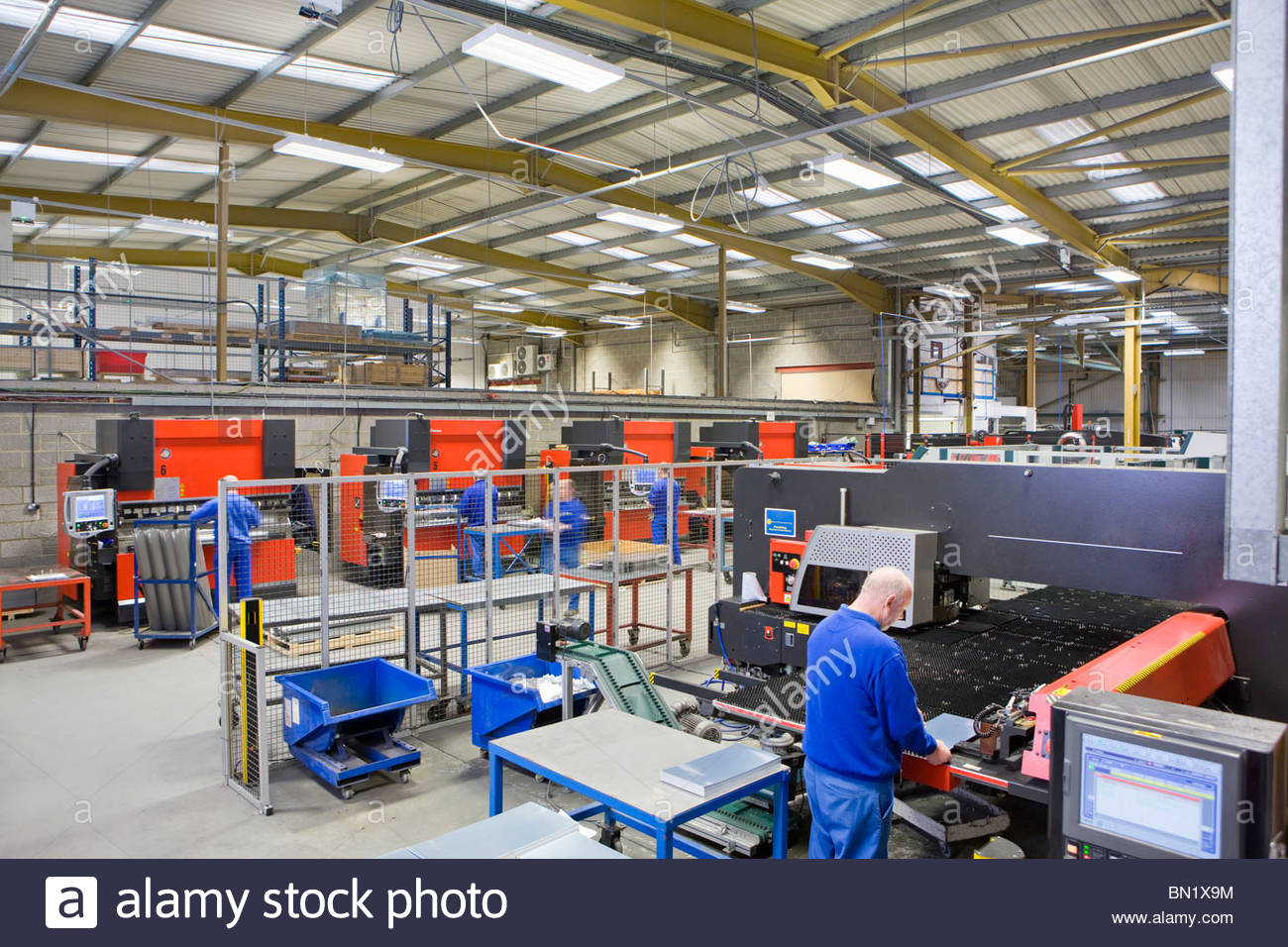 Worker inspecting aluminium light fitting at machinery in factory - Stock Image