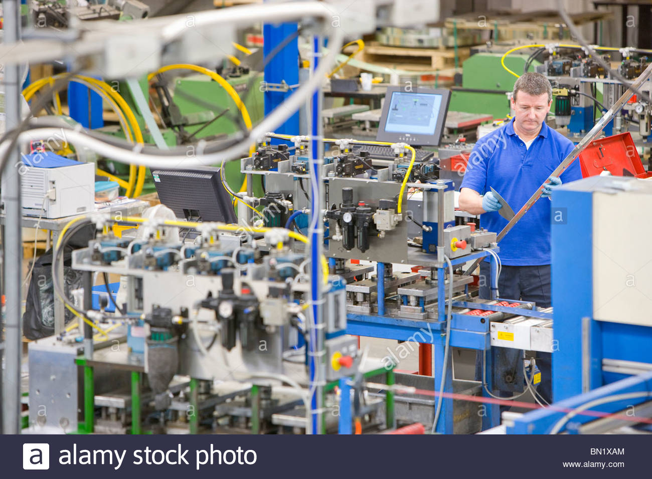 Worker inspecting aluminium light fitting near machinery in factory - Stock Image