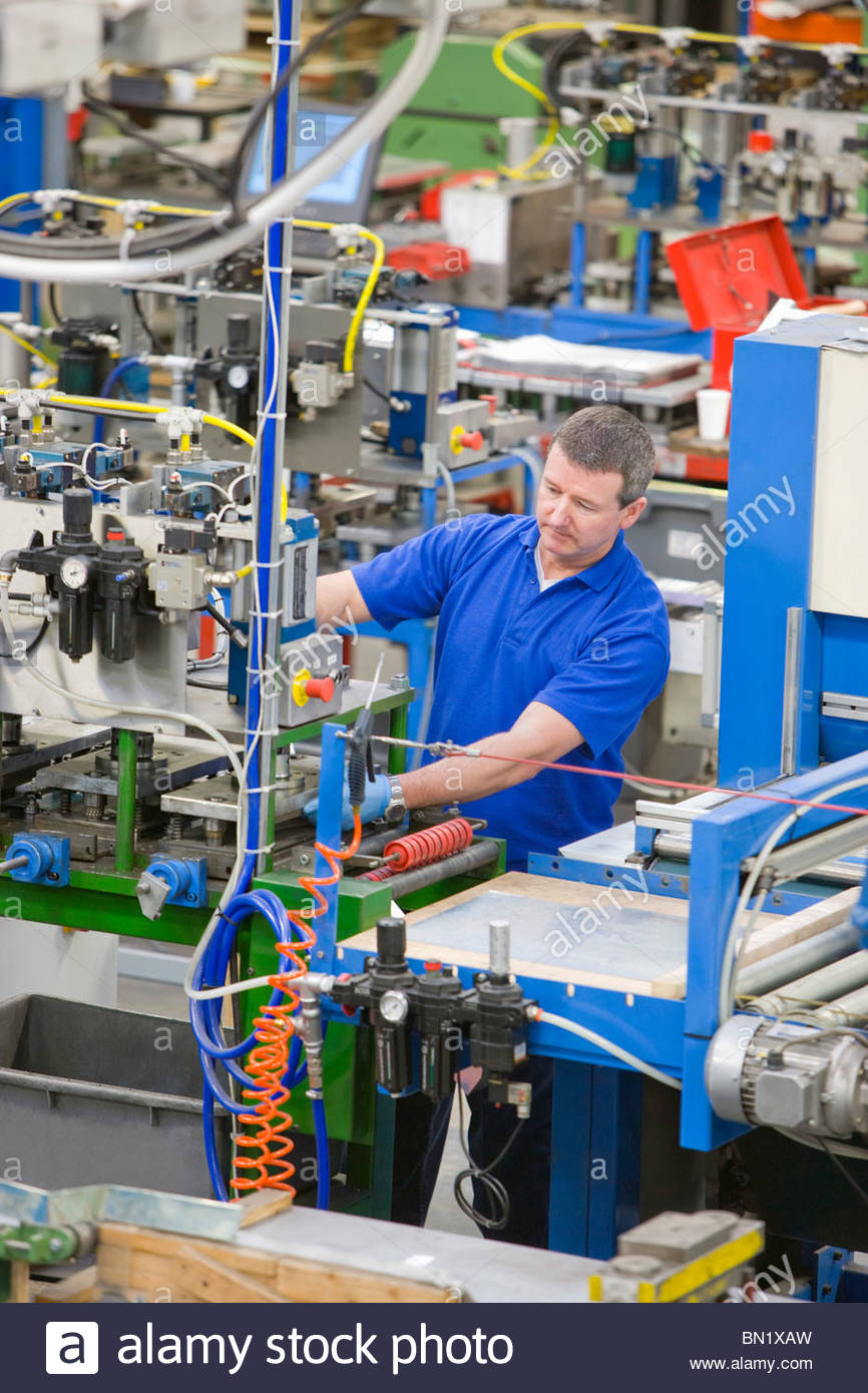 Worker operating machinery on production line in factory that manufactures aluminium light fittings - Stock Image