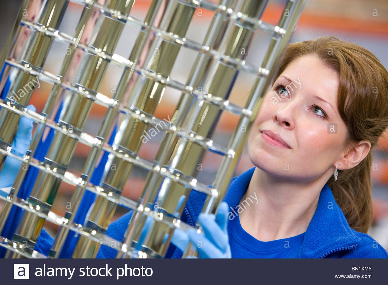 Worker inspecting aluminium light fittings in factory - Stock Image