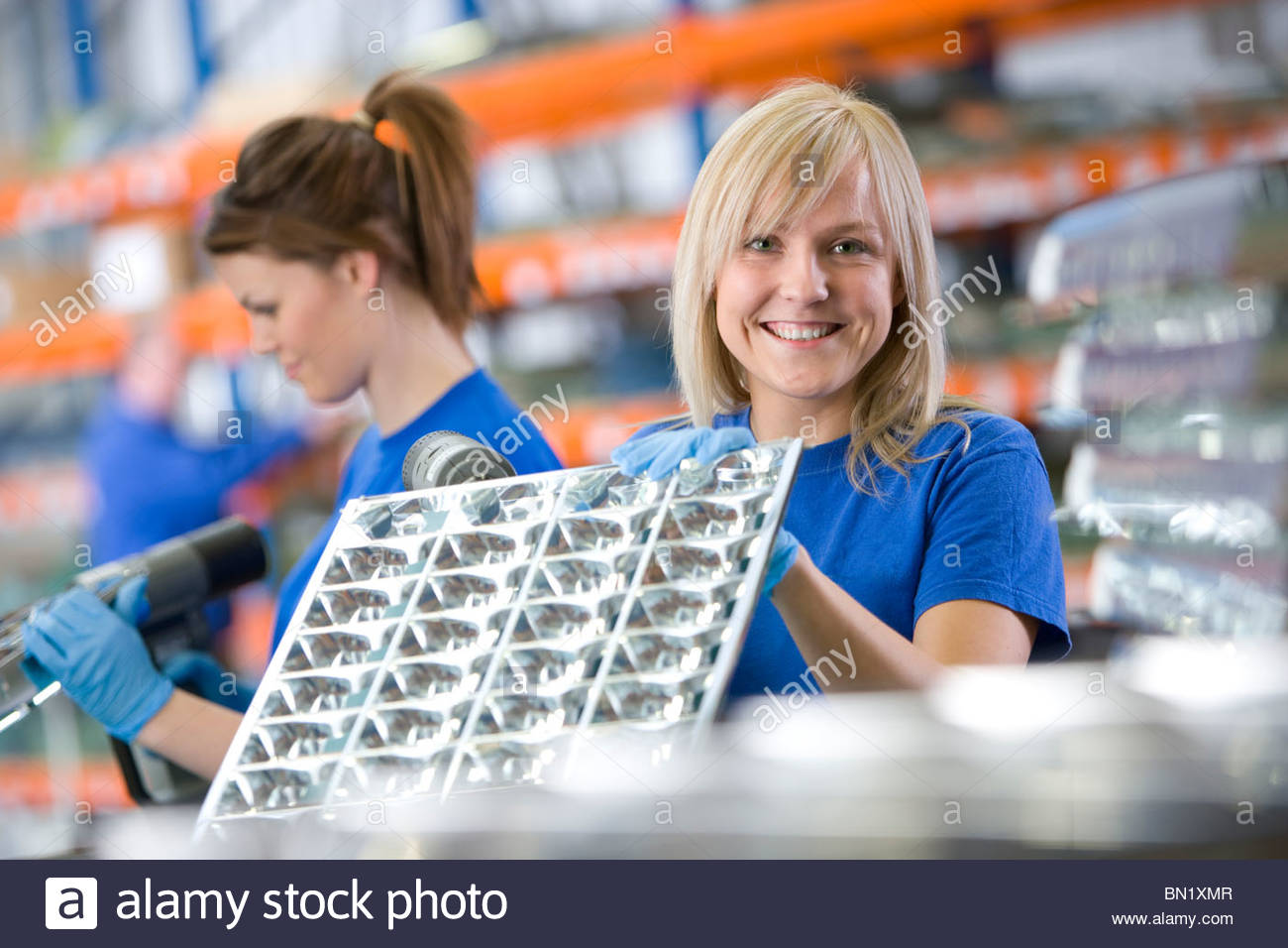 Portrait of smiling worker holding aluminium light fittings in factory - Stock Image