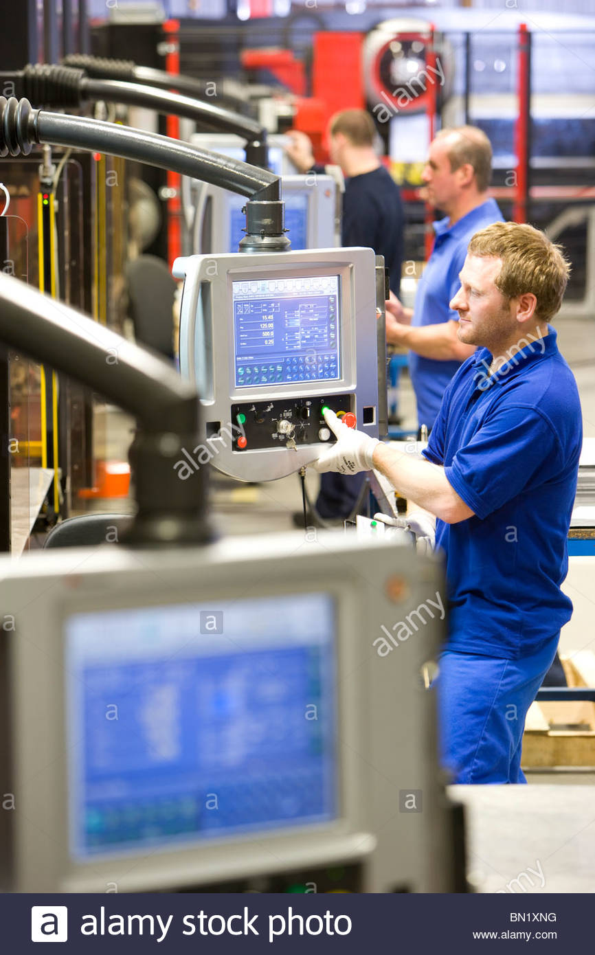 Workers operating computer controlled machinery in factory that manufactures aluminium light fittings - Stock Image